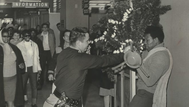 A sheriff's deputy pins Lawrence Friend (right) against the wall while the two wrestle over a Christmas tree during a sit-in demonstration at the Milwaukee County welfare center on Dec. 5, 1968. The scuffle developed when a spokesman for the group grabbed the office tree and Friend came to her aid. Fourteen people were arrested. The photo was published in the Dec. 6, 1968, Milwaukee Journal.