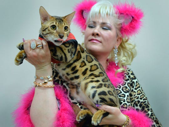 An owner poses with her Bengal cat.