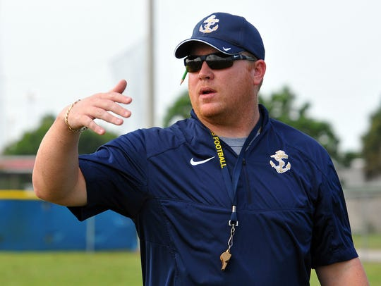 Eau Gallie High head coach Tim Powers talks with his players during a practice on the school's football practice field.
