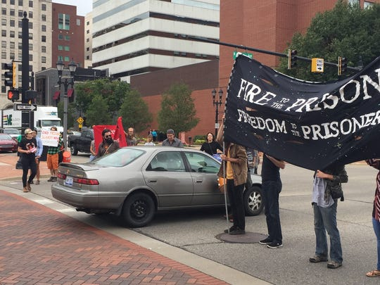 A vehicle passes through a line of demonstrators who had blocked traffic on Grand Avenue at East Michigan Avenue on the afternoon of Friday, Aug. 18, 2017. No one was injured.