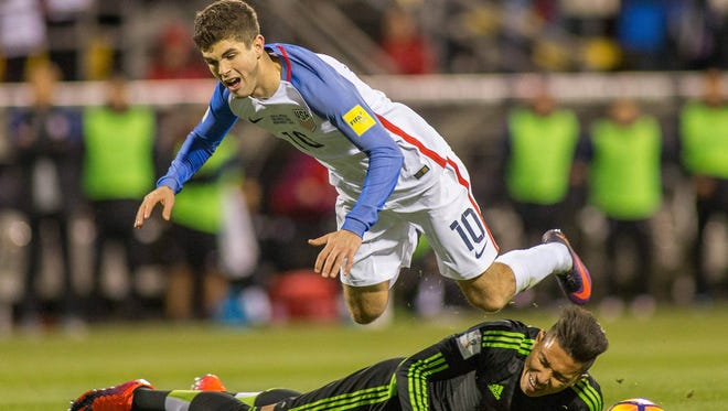Christian Pulisic is fouled by Mexico defender Carlos Salcedo during a match in 2016.