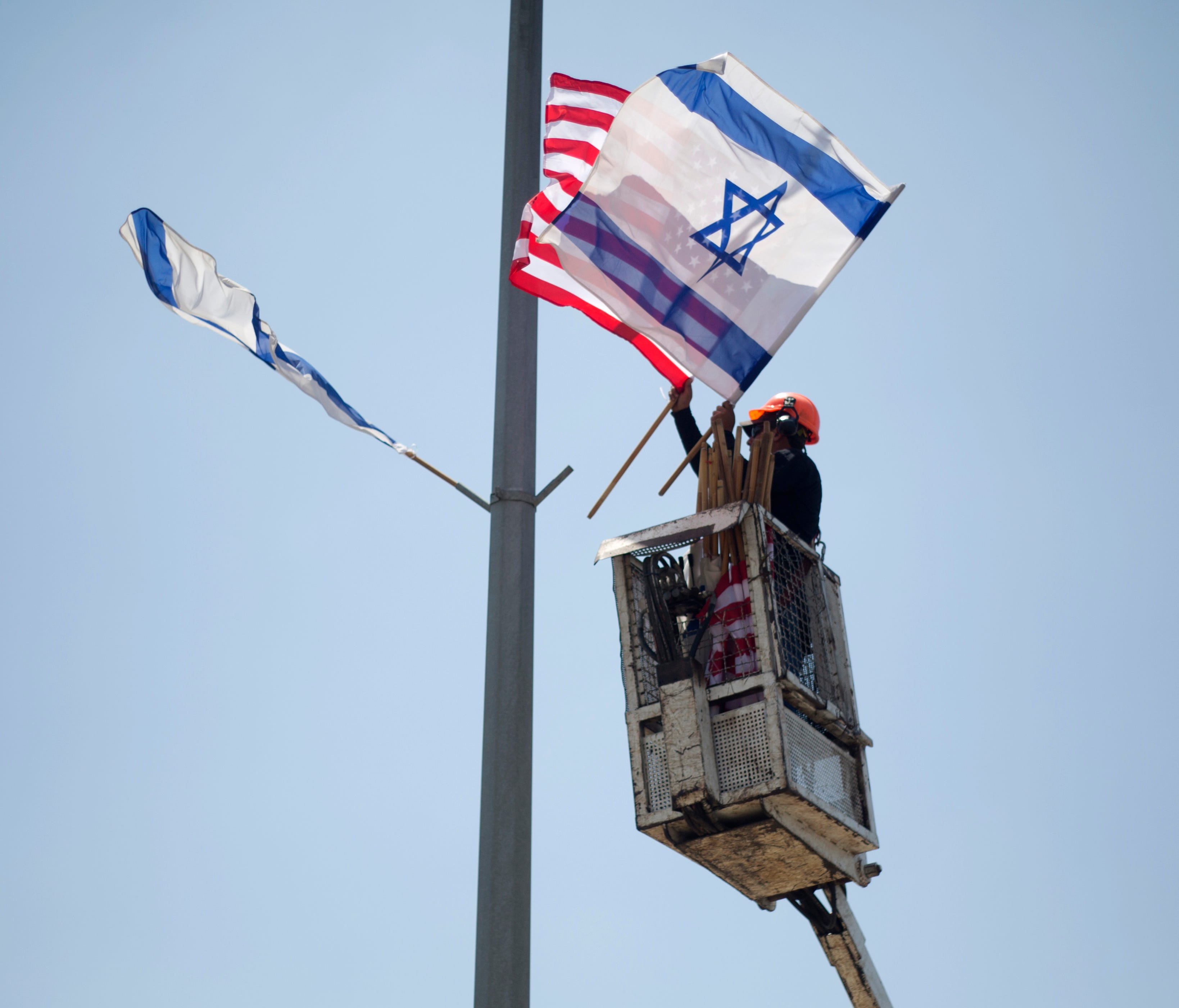 A worker hangs Israeli and U.S. flags on a lamppost along a freeway leading to Jerusalem, days before a planned visit by President Trump,  May 16, 2017.