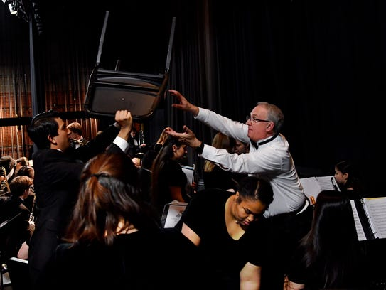 A student passes a chair to Abilene High School band director Paul Walker prior to the honor band's performance at Tuesday night's spring concert. Walker is retiring after 28 years as a band instructor, 21 of them at Abilene High