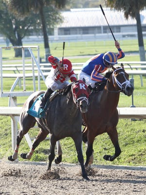 Miguel Mena, left, aboard International Star, outduels Stanford on the rail, to win the Louisiana Derby (Grade II) at the Fair Grounds Race Course in New Orleans, LA, Saturday, March, 28, 2015.