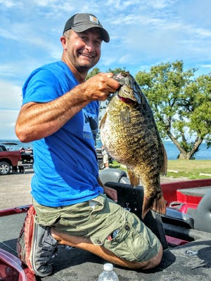 Patrick Hildenbrand, a sergeant with the Red Hook police department, shows off the smallmouth bass he caught in the St. Lawrence River in this file photo. The 8-pound, 4-ounce fish tied a state record.