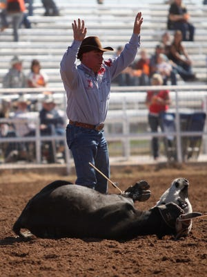 Guy Allen, of Santa Anna, Texas, gives the signal to stop his time during the 2011 Steer Roping competition at the San Angelo Fairgrounds Arena. (Standard-Times file photo)