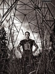 Mason Salley of Central Kitsap is shown in black and white, framed by a power grid tower in his senior portrait.