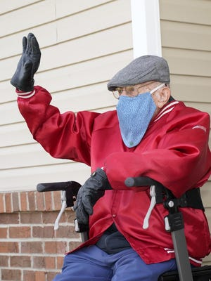 Charlie Peart waves to those in the parade that passed by his apartment on Sunday in Onsted. Peart turned 100 on Monday.