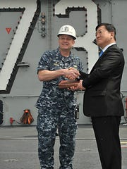 Grand Ledge native Capt. Greg Fenton, left, receives a gift from Young Dae Lee, Rep. of Korea Ministry of National Defense deputy minister, during a tour of the ship several years ago.