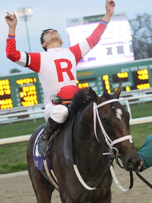 Jockey Miguel Mena looks to the heavens after winning the Risen Star Stakes, (GrII) aboard International Star at the Fair Grounds in New Orleans, LA Saturday, February 21, 2015. Photo by Lou Hodges, Jr. / Hodges Photography