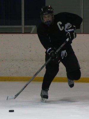 Livonia Churchill defenseman Luke Justice passes the puck during a Tuesday afternoon practice drill.