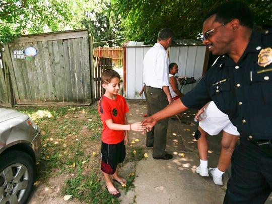 An Indianapolis police officer shakes a young boy's hand during the public safety walk.