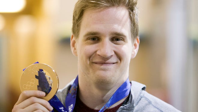 Coyotes forward Lauri Korpikoski holds his bronze medal for Team Finland in the 2014 Olympic Games in Sochi for hockey, following a Coyotes' practice at the Ice Den in Scottsdale on Wednesday, February 26, 2014.