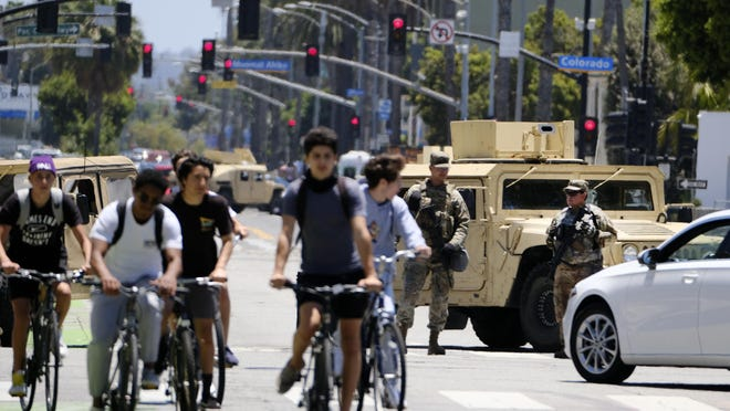 Cyclists ride down a street past a road block with National Guard troops along Ocean boulevard in Santa Monica on Sunday.  Officials announced Sunday that National Guard troops will be pulled out of California cities where they've been deployed for a week after rampant violence and thievery marred the first days of protests over the death of George Floyd.
