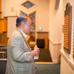 David Miller of Salisbury stands before the memorial plaques from the Congregation of Israel in Pocomoke City. The plaques contain the names of Miller's ancestors. The plaques were re-dedicated and now reside in the sanctuary of Temple Bat Yam in Berlin.