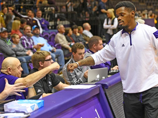 NSU basketball guard Jalan West fist bumps David Antilley before a basketball game against McNeese on Dec. 31 in Prather Coliseum. Antilley and his son Davey have served in various roles at NSU athletics for nearly 30 years.