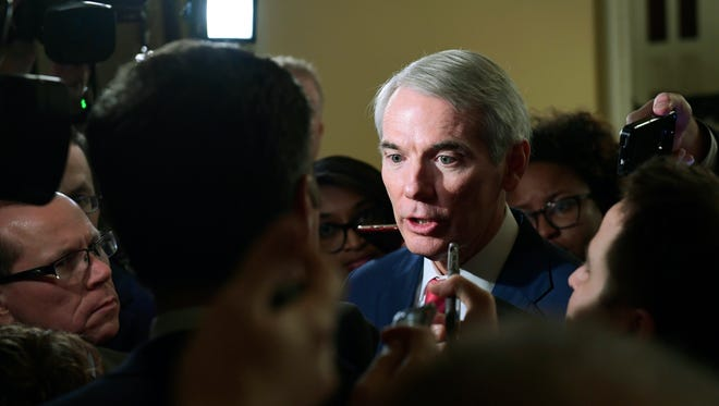 Reporters gather around Sen. Rob Portman, R-Ohio, on Capitol Hill in Washington, Friday, Dec. 15, 2017, as they ask questions on the progress of an agreement on a sweeping overhaul of the nation's tax laws. (AP Photo/Susan Walsh)