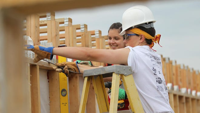 Kayla Fox, 17, and Conor Fitzpatrick, 17, of Northbrook, Ill., work on a Habitat for Humanity house on Primrose Court on Wednesday.