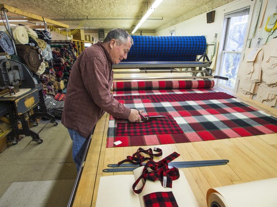 Jeff White cuts a section of flannel for a dog bed at Johnson Woolen Mills in Johnson. All the cutting and assembly at the mill is done by hand.