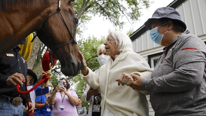 Joyce Patterson, in the white sweater, is treated to a visit by Hank, a 28-year-old quarter horse, as she celebrates her 100th birthday Monday, Aug. 3, 2020, at her home in Rockford. The visit was arranged by BraveHearts Therapeutic Riding and OSF HealthCare.
