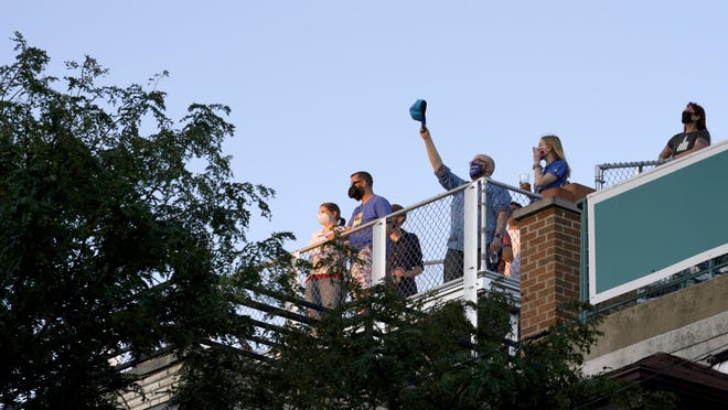 Patrick McCarron raises his Chicago Cubs cap from a rooftop venue Sept. 4 toward Wrigley Field after the national anthem before a baseball game between the Cubs and St. Louis Cardinals in Chicago. The coronavirus pandemic has been especially hard on businesses that rely on ballpark traffic, eliminating crowds at major league games and leading to rules that limit the amount of people they can have inside their doors.