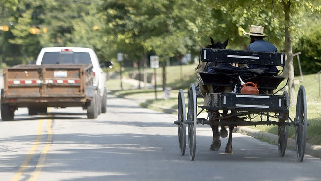A truck pulling a trailer passes an Amish wagon on Sandusky Street on Wednesday.