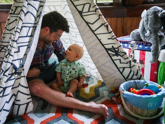 Travis Harris plays with 10-month-old Bly in a tent set up in the living room of their San Angelo home Monday, June 11, 2018.
