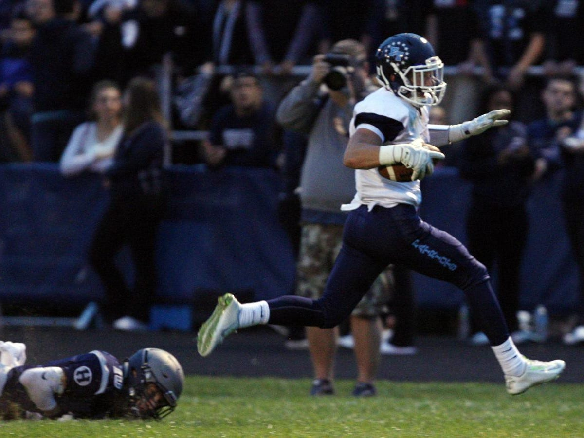 Adrian Rybaltowski, #4 Freehold Township, breaks free of Nic Rossi, #10 Howell, on his way to scoring a touchdown in a football game Friday, September 25, 2015, at Howell High School.