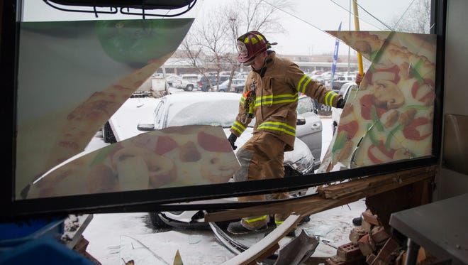 Waynesboro firefighters respond the scene of an accident where an elderly driver crashed through the front of a Domino's Pizza on Monday, Feb. 16, 2015.