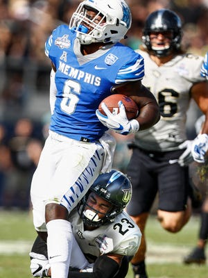 Memphis running back Patrick Taylor Jr. (left) fights for a first down against UCF defender Tre Neal (right) during second quarter action of the the AAC Championship football game in Orlando, Fl., Saturday, December 2, 2017.