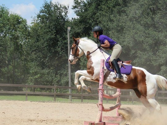 Dexria Sapp practices jumping on her horse.