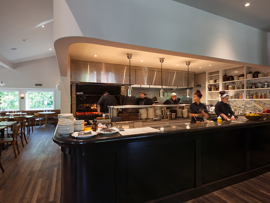 The restaurant is centered around a blazing wood-fired grill and open kitchen.