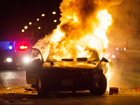 A car burns as a crowd of more than 100 people gathers