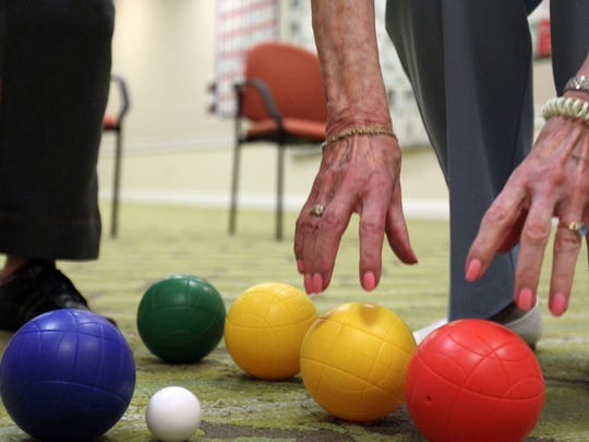 A participant picks up her balls as residents of Arbor