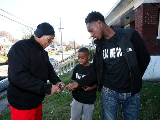 Community activist Christopher 2X, left,  examined a flier with Ki'Anthony Tyus, 10, and Diontae Reed, 14, in the Shawnee neighborhood.  They are part of the Hood 2 Hood campaign to end violence in the community.  Ki'Anthony and Diontae both survived separate shootings earlier this year.
