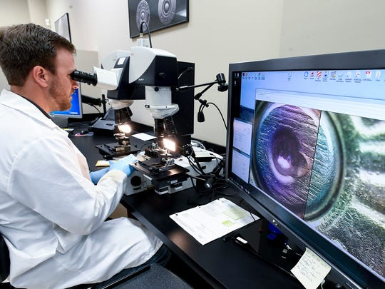 Forensic Scientist Associate Michael Dugan uses a comparison microscope at the Alabama Department of Forensic Sciences in Montgomery, Ala. on Tuesday May 29, 2018.