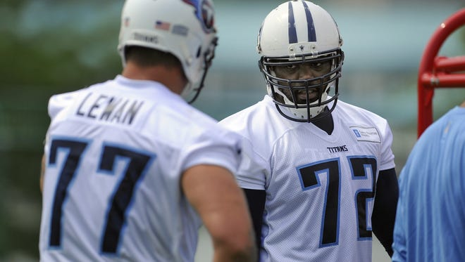 Tackles Michael Oher, right, and Taylor Lewan talk during practice at Saint Thomas Sports Park in May.