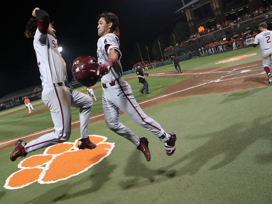Drew Mendoza, left, celebrates Steven Wells Jr.'s home run in the 13th inning aagainst Clemson at Doug Kingsmore Stadium in Clemson, S.C. on Saturday, May 5, 2018.