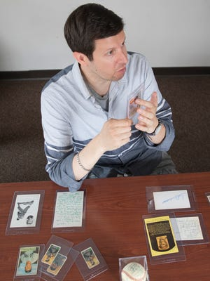 Michael Osacky, a nationally known sports card and memorabilia appraiser, shows baseball cards he has appraised while visiting Chillicothe last week.