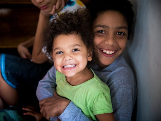 Aubrey Bailey, 10, holds his sister Tempest, 2, in