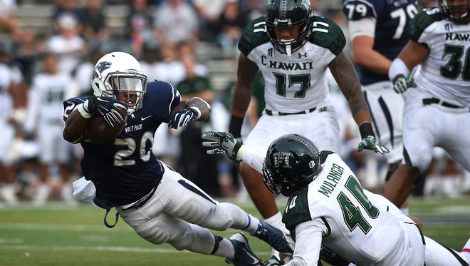 Nevada's James Butler (20) falls forward for a first down past Hawaii's Dany Mulanga (40) during their football game at Mackay Stadium on Saturday.