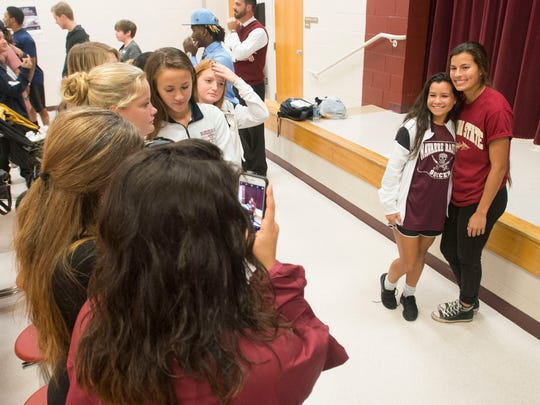 Navarre High School soccer star, Emily Madril, far right, takes pictures with her teammates during a celebration at the south Santa Rosa high school Monday afternoon. Madril will be leaving high school at the end of the month to join the Florida State University Soccer team in January.