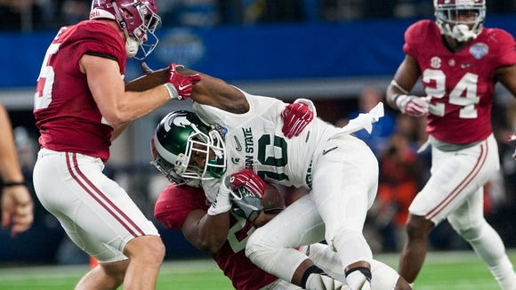 Michigan State wide receiver Aaron Burbridge (16)  is stopped by Alabama linebacker Dillon Lee (25) and linebacker Shaun Dion Hamilton (20) during first half action in the Cotton Bowl on Thursday December 31, 2015 at AT&T Stadium in Arlington, Tx.
