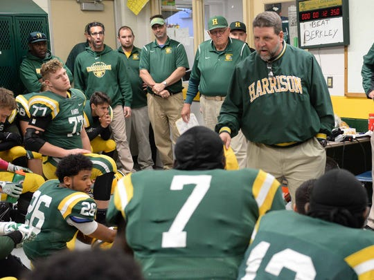 Harrison's defensive coordinator Dave Thorne, who also played football for the Hawks, gives the 2017 squad a pep talk prior to a game.