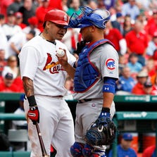 May 15, 2014; St. Louis, MO, USA; St. Louis Cardinals catcher Yadier Molina (4) has words with Chicago Cubs first base coach Eric Hinske (2) after nearly getting hit by a high pitch during the eighth inning at Busch Stadium. The Cardinals won 5-3. Mandatory Credit: Scott Kane-USA TODAY Sports