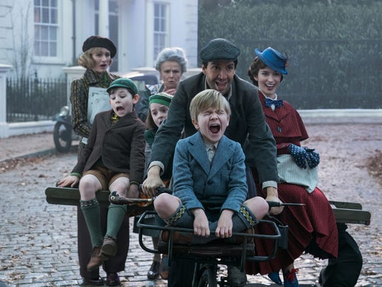 "Jane (Emily Mortimer, left), John (Nathanael Saleh), Annabel (Pixie Davies), Ellen (Julie Walters), Jack (Lin-Manuel Miranda), Georgie (Joel Dawson) and Mary Poppins (Emily Blunt) are joyriding and singing in ""Mary Poppins Returns."""