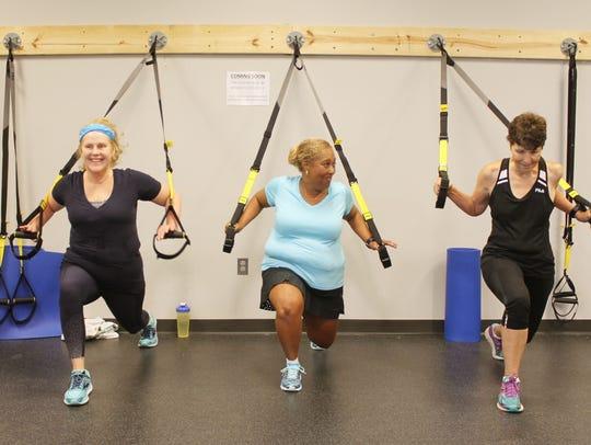 Fitness instructor Sharon Jones (center) encourages