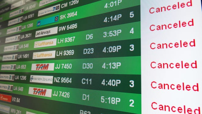 """The flight status screen flashes """"Canceled"""" notices at the Dulles International Airport in the Virginia suburbs of Washington, D.C., on  Feb. 13, 2014."""