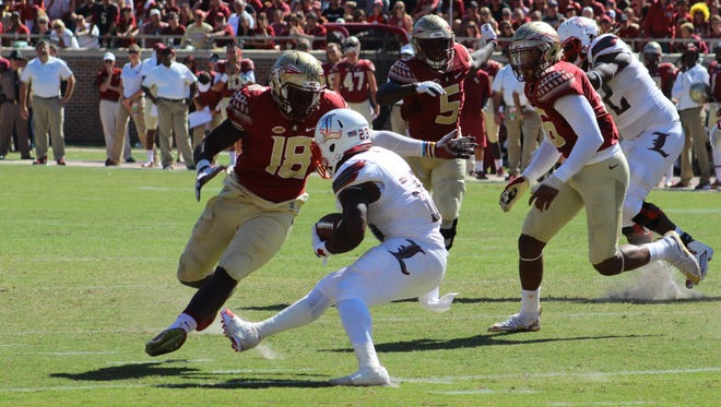 Ro'Derrick Hoskins (18) tracks down Brandon Radcliff (23). Florida State defeated Louisville 41-21 on Saturday, October 17, 2015 in Doak Campbell Stadium.