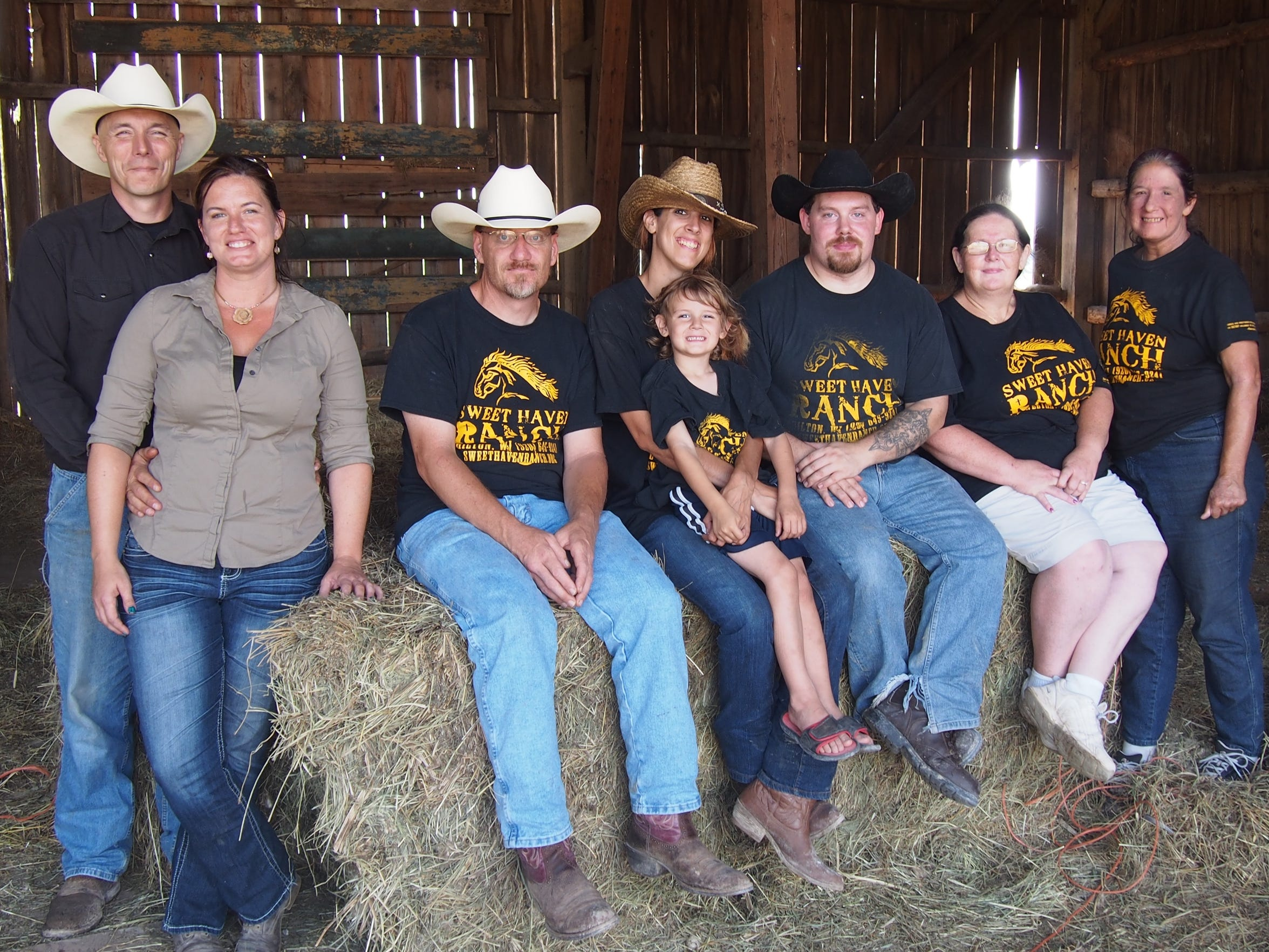 Ward, left, and his fiance pose with volunteers on a hay bale.